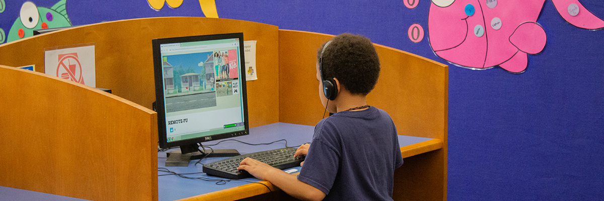 Young boy using desktop computer in library