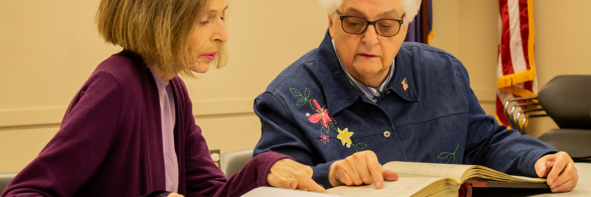 Two Women looking into old book during genealogy class