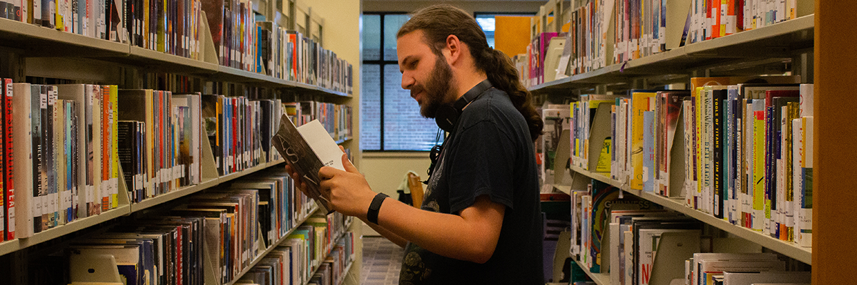 Man reading book in library book stacks