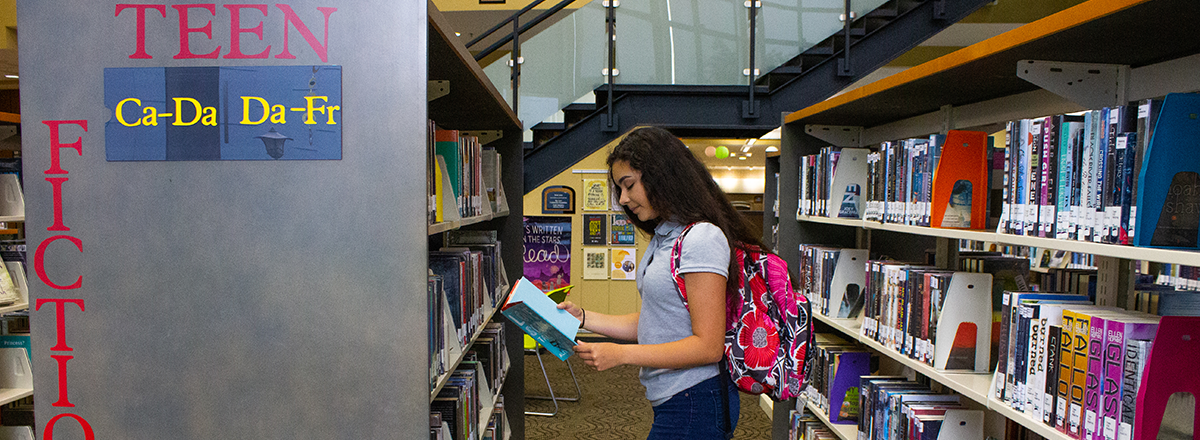 Teen girl browsing the teen fiction section of library