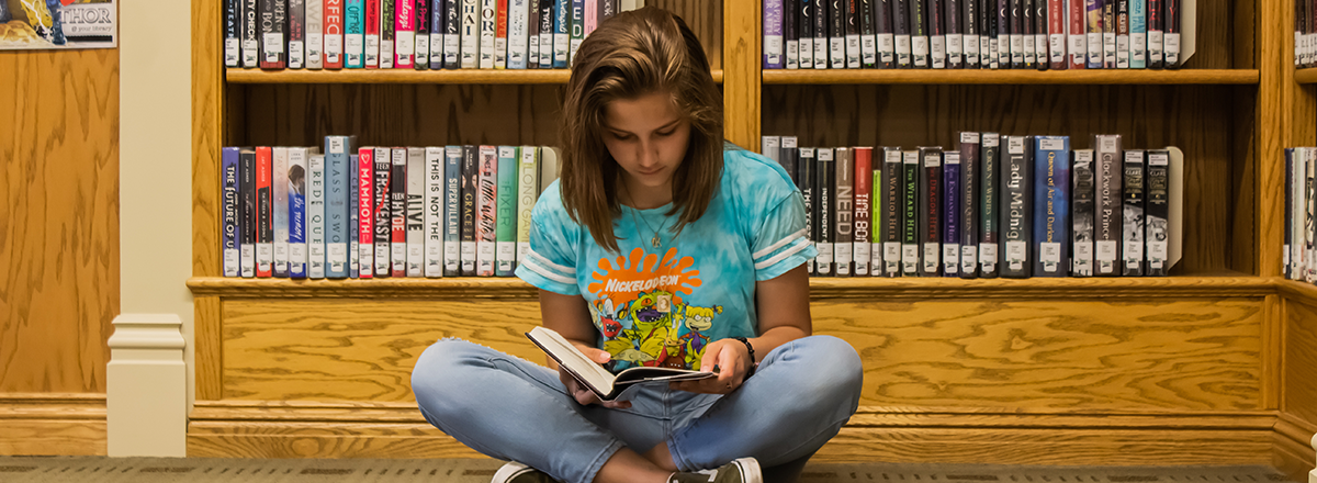 Teen reading a book while sitting on library floor